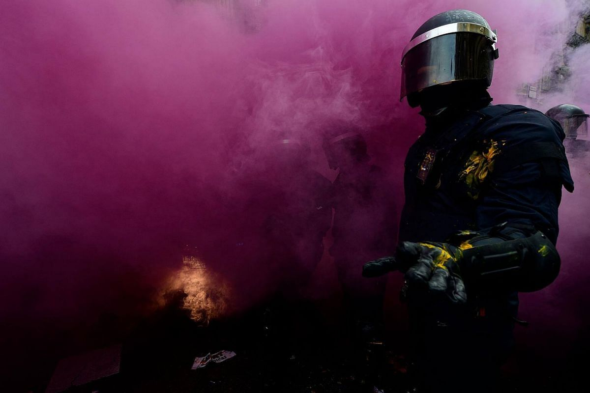 A riot police officer gestures after a smoke bomb was thrown during scuffles with protesters during a demonstration in Barcelona, on March 25, 2018.