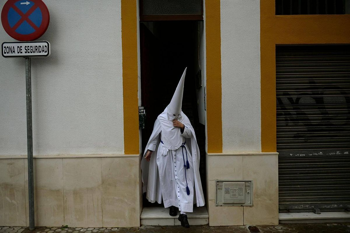 A penitent of the La Paz brotherhood heads to church to take part in the Palm Sunday procession in Sevilla at the start of the Holy Week, on March 25, 2018.