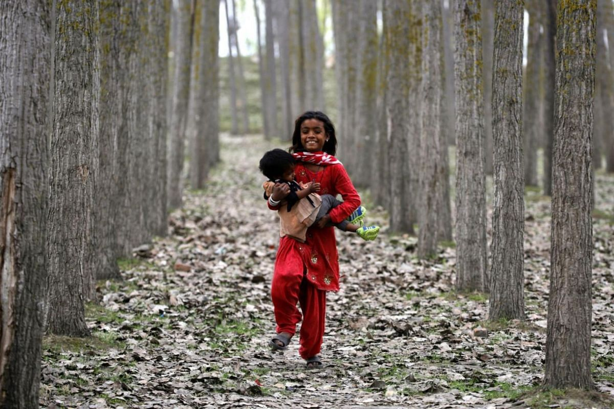 A child walks with a baby in her arms towards a temporary tent on the outskirts of Srinagar, the summer capital of Indian Kashmir, on March 27, 2018.