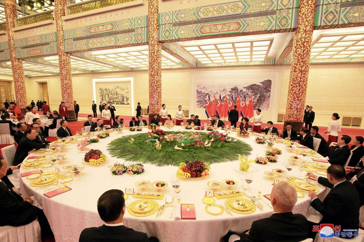 North Korean leader Kim Jong Un and wife Ri Sol Ju, and Chinese president Xi Jinping and wife Peng Liyuan attend a banquet during Mr Kim's unofficial visit to China.