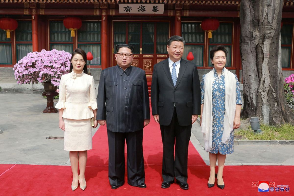 North Korean leader Kim Jong Un (second from left) and wife Ri Sol Ju (left), and Chinese president Xi Jinping (second from right) and wife Peng Liyuan (right) pose for a photo during Mr Kim's unofficial visit to China.