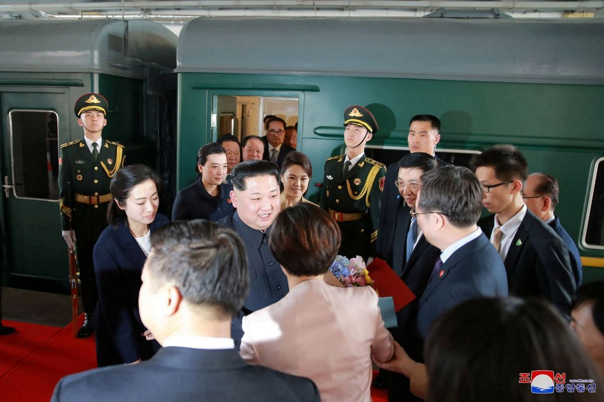 North Korean leader Kim Jong Un and his wife Ri Sol Ju are seen near a train during Mr Kim's unofficial visit to China.