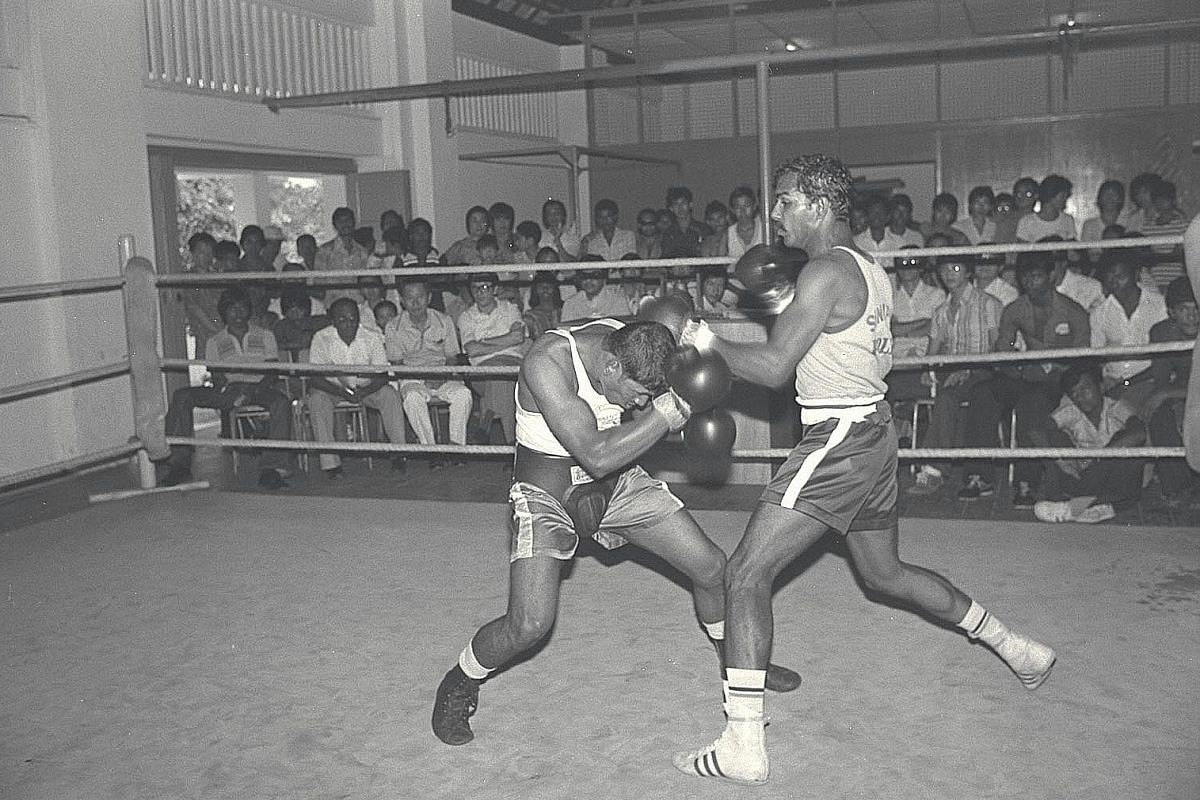 A full crowd watching light-welterweight G. Mahadevan (right) hold Haridas at bay in a boxing trial at the Farrer Park gymnasium.