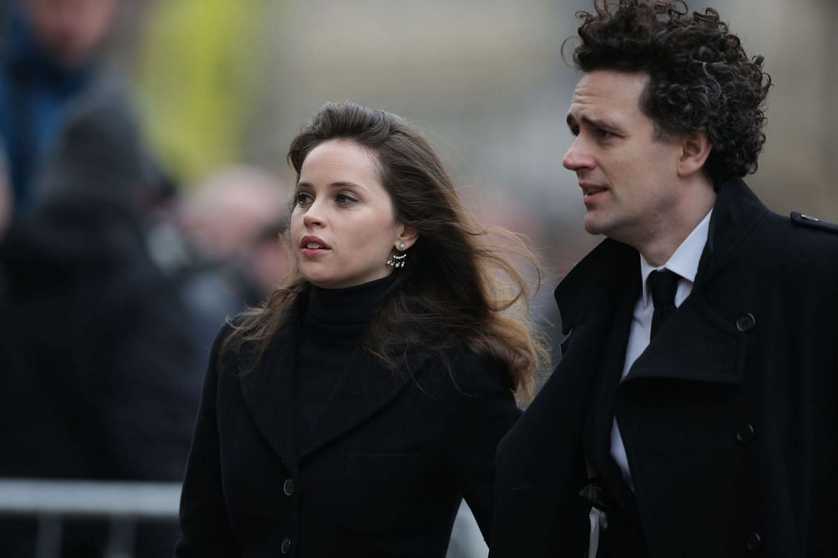 British actress Felicity Jones, who played Stephen Hawking's wife in The Theory Of Everything, and her partner Charles Guard arrive to attend the funeral of the British scientist at the Church of St Mary the Great in Cambridge on March 31, 2018.