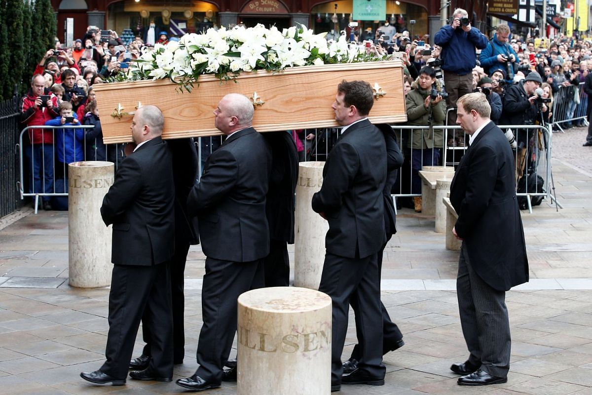 Pallbearers carry the coffin of British scientist Stephen Hawking into Great St Mary's Church in Cambridge, where his funeral is being held, on March 31, 2018.