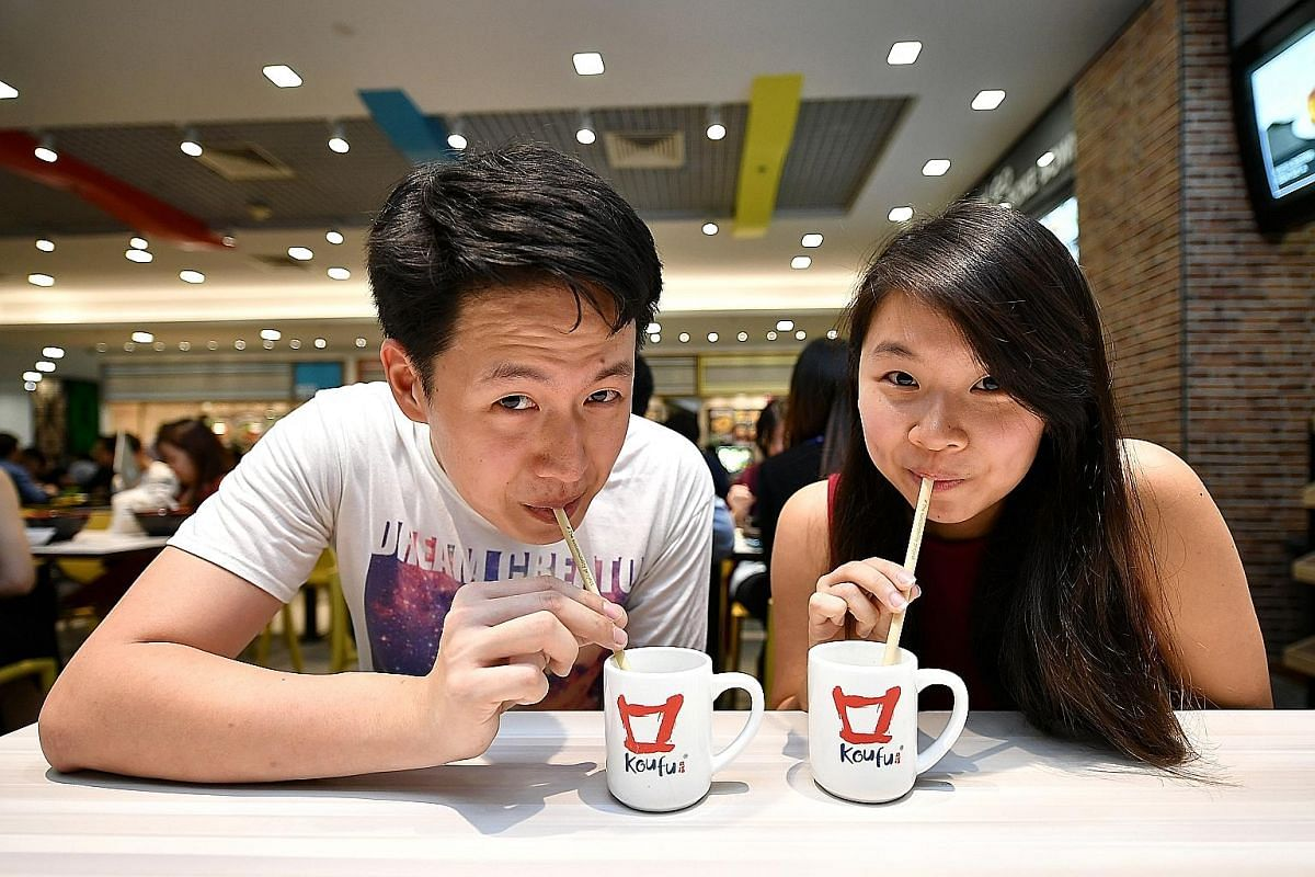 Singapore Management University students Chia Chong Cher and Joline Tang drink from bamboo straws at the Koufu food court on their campus.