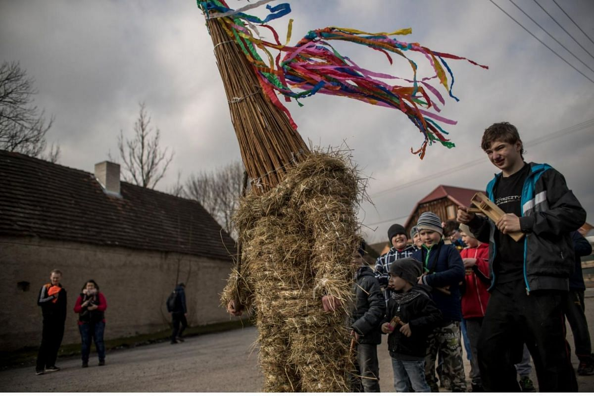 A boy dressed in hay suit accompanied by peers with wooden rattles walks through the streets during an Easter procession called Marching Judas in the village of Stradoun, Czech Republic.