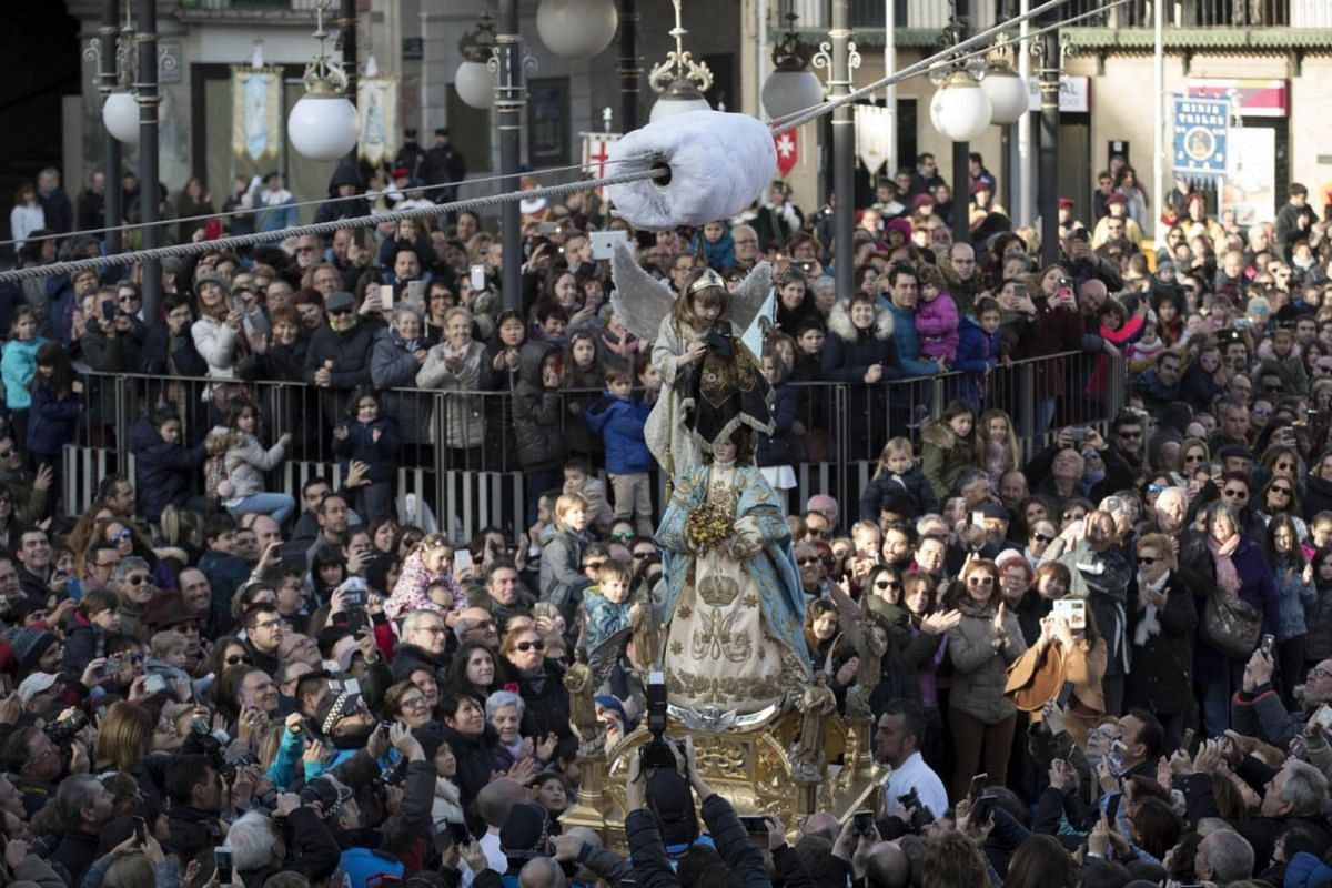 A young girl dressed as an angel unveiling a statue of the Virgin Mary after descending from the Clock House over the Plaza de los Fueros square in Tudela, Navarra, northern Spain.