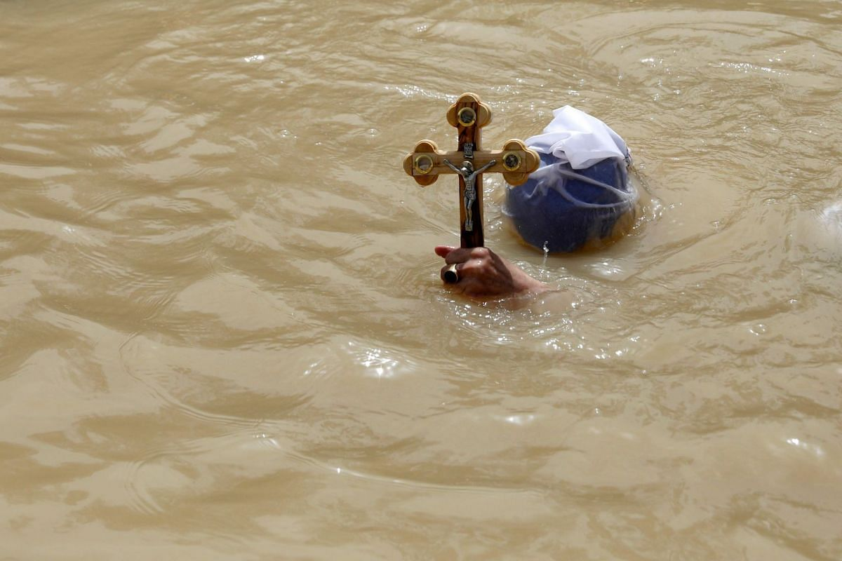A Moldovian Christian Orthodox pilgrim submerges in the waters of the Jordan River on April 3, 2018, at the Qasr al- Yahud baptismal site near the West Bank city of Jericho.
