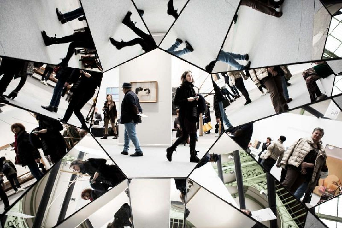 Visitors are reflected in an artwork by Swiss artist Simon Deppierraz at the Paris Art Fair in Paris, on April 5, 2018.