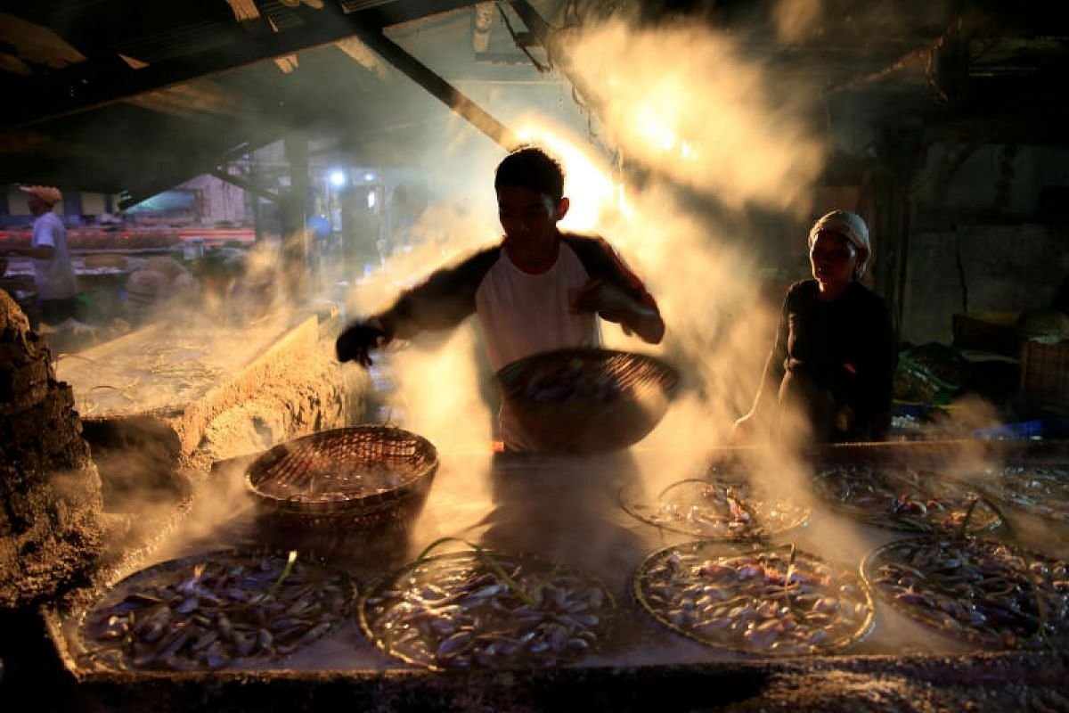 A worker is seen marinating fish at Cilincing district in Jakarta, Indonesia, on April 5, 2018.