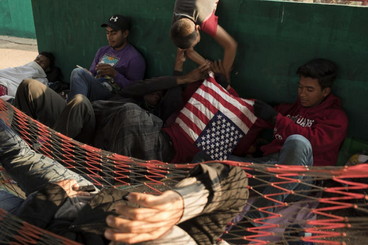 A group of Central American refugees and asylum seekers hold an American flag bandanna while taking shelter at the Community Sports Center in the town of Matias Romero, Oaxaca state, Mexico, on April 4, 2018.
