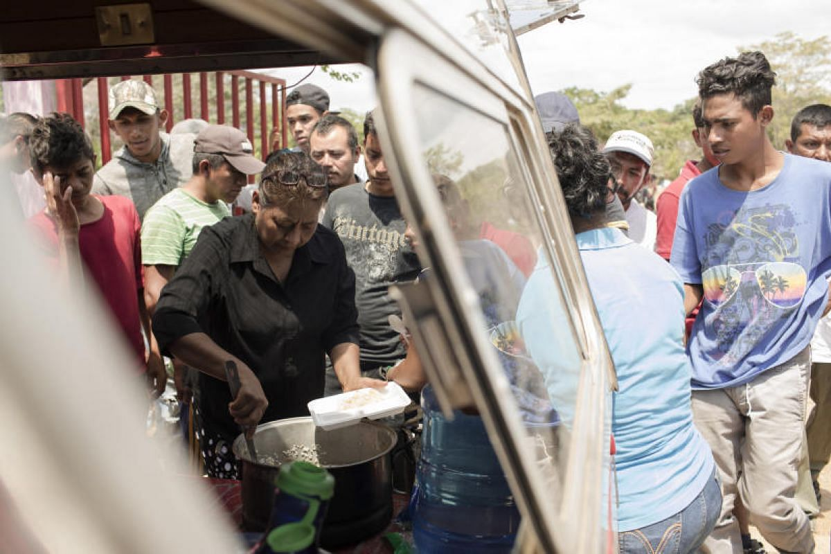 Local residents give out food to a group of Central American refugees and asylum seekers, in the town of Matias Romero, Oaxaca state, Mexico, on April 4, 2018.