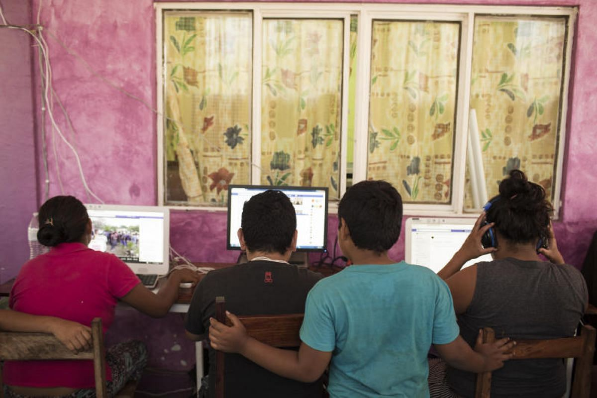 A group of Central American refugees and asylum seekers use computers at a locals residents home in the town of Matias Romero, Oaxaca state, Mexico, on April 4, 2018.