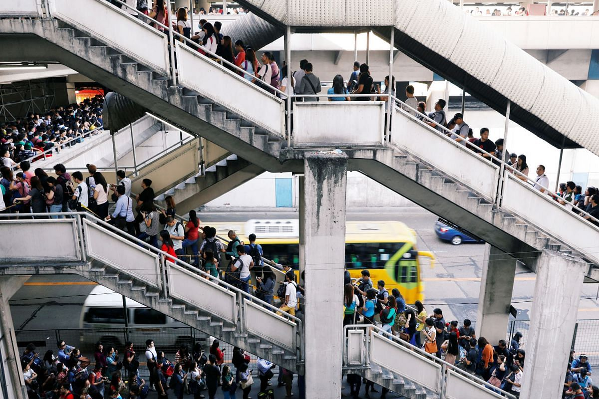 Commuters waiting to take the Metro Rail Transit during morning rush hour in North Avenue, Quezon City, part of Metro Manila. The rail system is already showing its age, says the writer. Heavy traffic in Makati City south of Manila, the densely popul