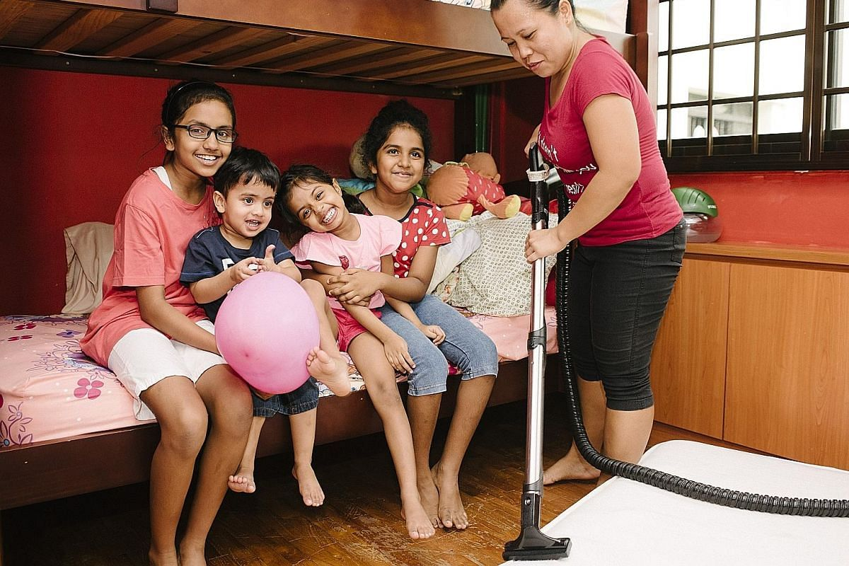 Ms Ashlyn Thia, with daughters Avalyn (left) and Emmalyn (right), separates adult laundry from the children's before each wash. The Clements get their domestic helper Gemmalyn Asistin, with children (from left) Julia, Abraham, Gloria and Alicia Sarah