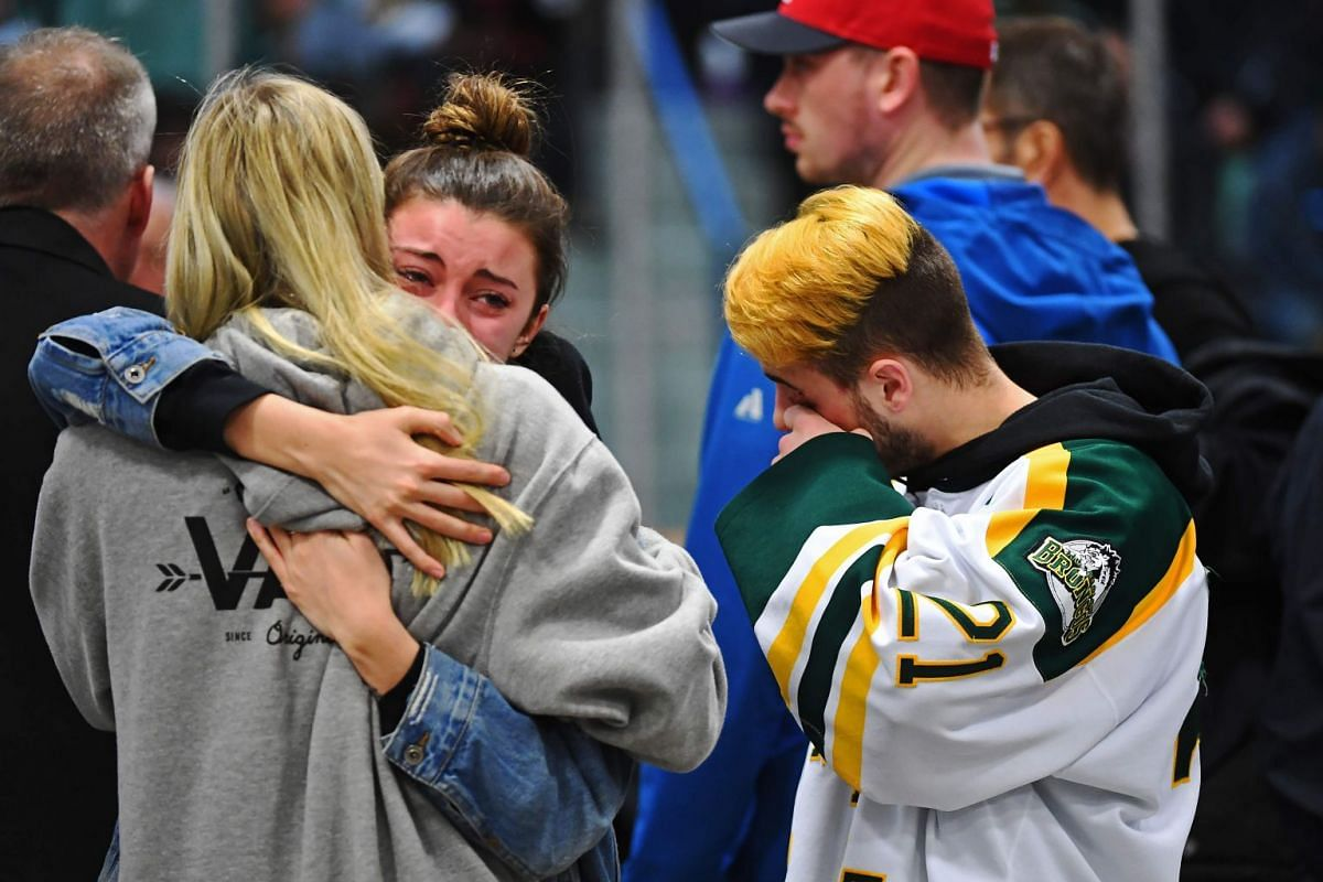 Mourners comfort each other during a vigil at the Elgar Petersen Arena, home of the Humboldt Broncos, to honour the victims of a fatal bus accident, April 8, 2018 in Humboldt, Canada. PHOTO: AFP