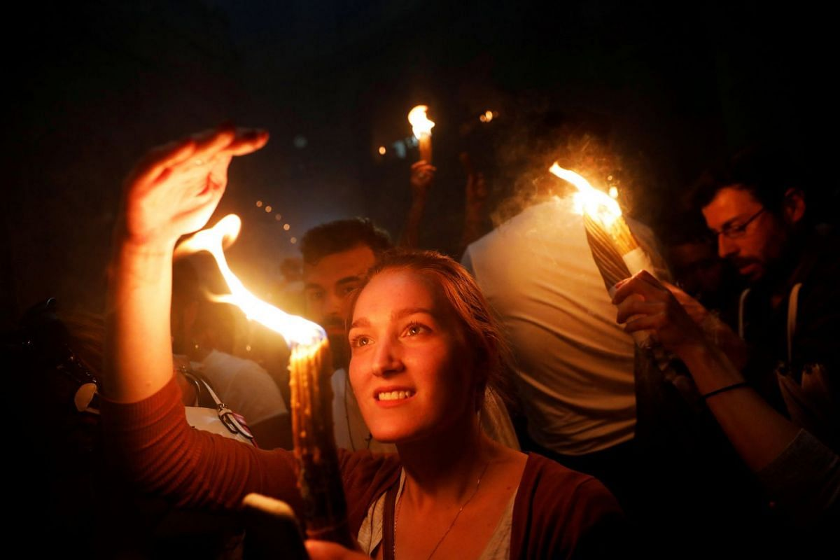 Worshippers hold candles as they take part in the Christian Orthodox Holy Fire ceremony at the Church of the Holy Sepulchre in Jerusalem's Old City April 7, 2018. PHOTO: REUTERS