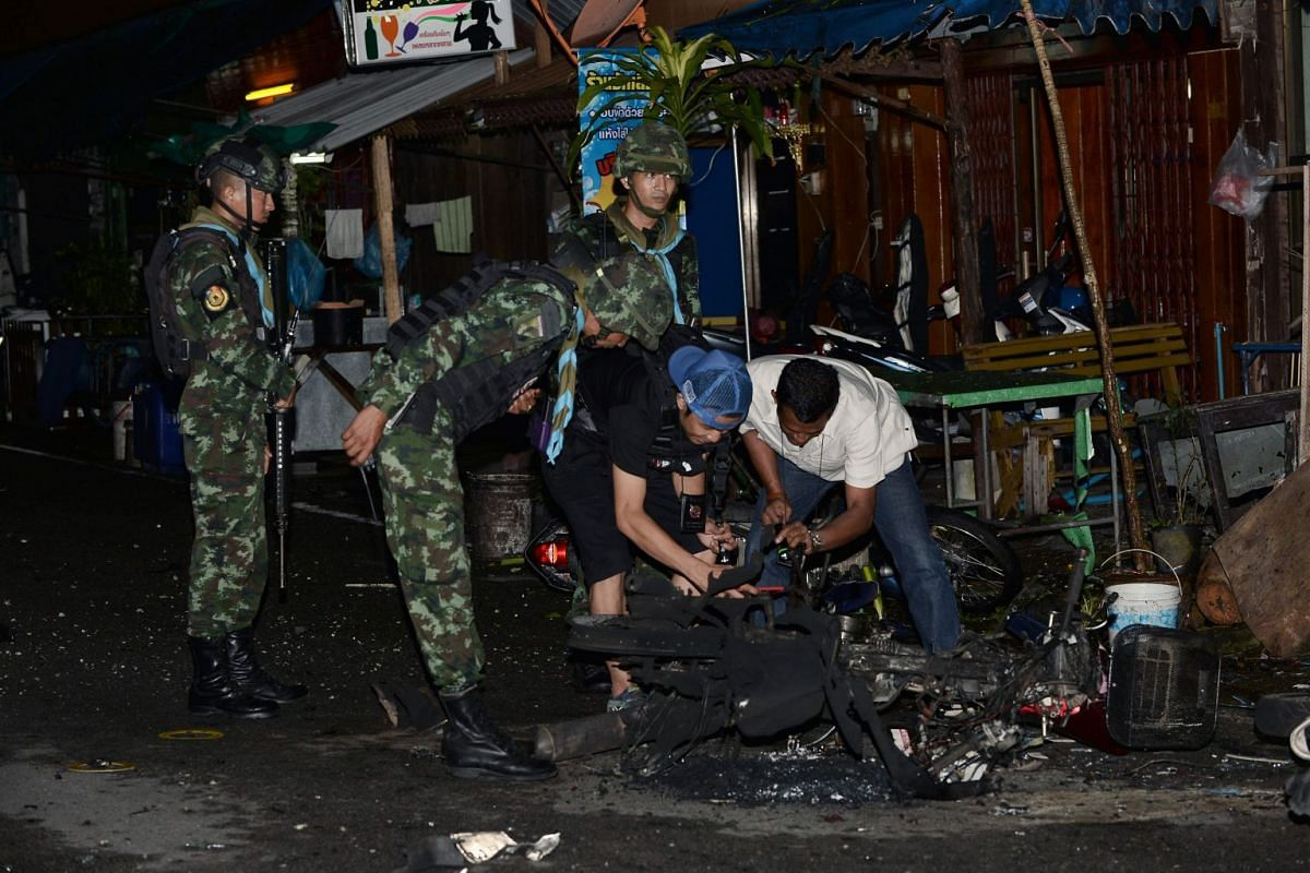 Soldiers and plain clothes members of a police bomb squad inspect the wreckage of a motorcycle at a blast site in Sungai Kolok, Narathiwat province, on April 9, 2018. PHOTO: AFP