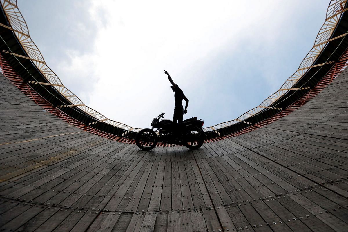 """A stuntman performs a test ride on a motorcycle inside the """"Well of Death"""" arena during a fair in Bhaktapur, Nepal April 9, 2018. PHOTO: REUTERS"""
