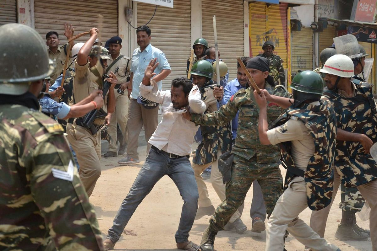 Police beat a protester during a strike observed across India against a caste-based reservations system in education and jobs in Gaya in Bihar state on April 10, 2018. PHOTO: AFP