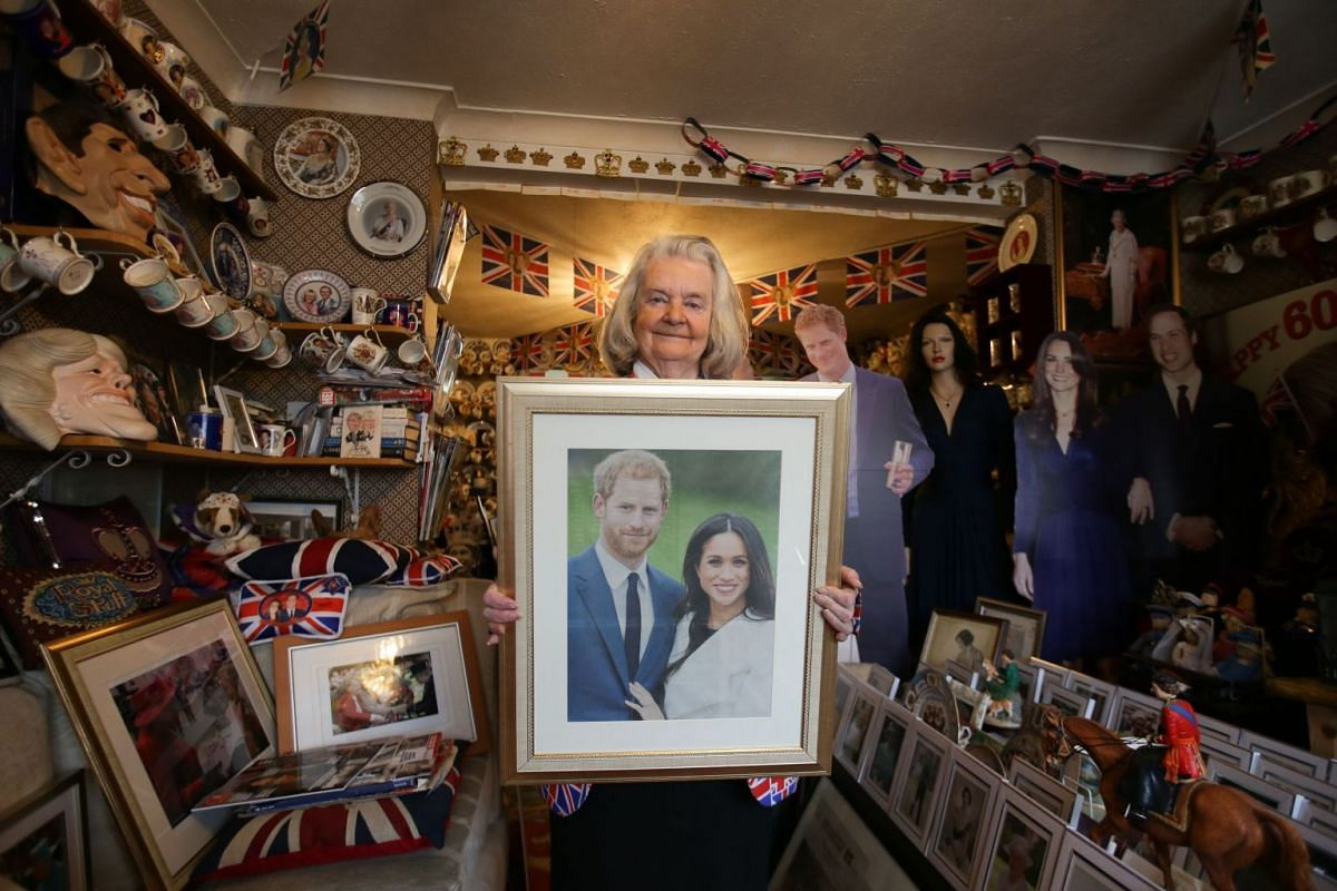 A photo released on April 11, 2018 shows royal fan Margaret Tyler posing with a framed photograph of Britain's Prince Harry and his fiancee Meghan Markle, at her home in north London on April 4, 2018. PHOTO: AFP