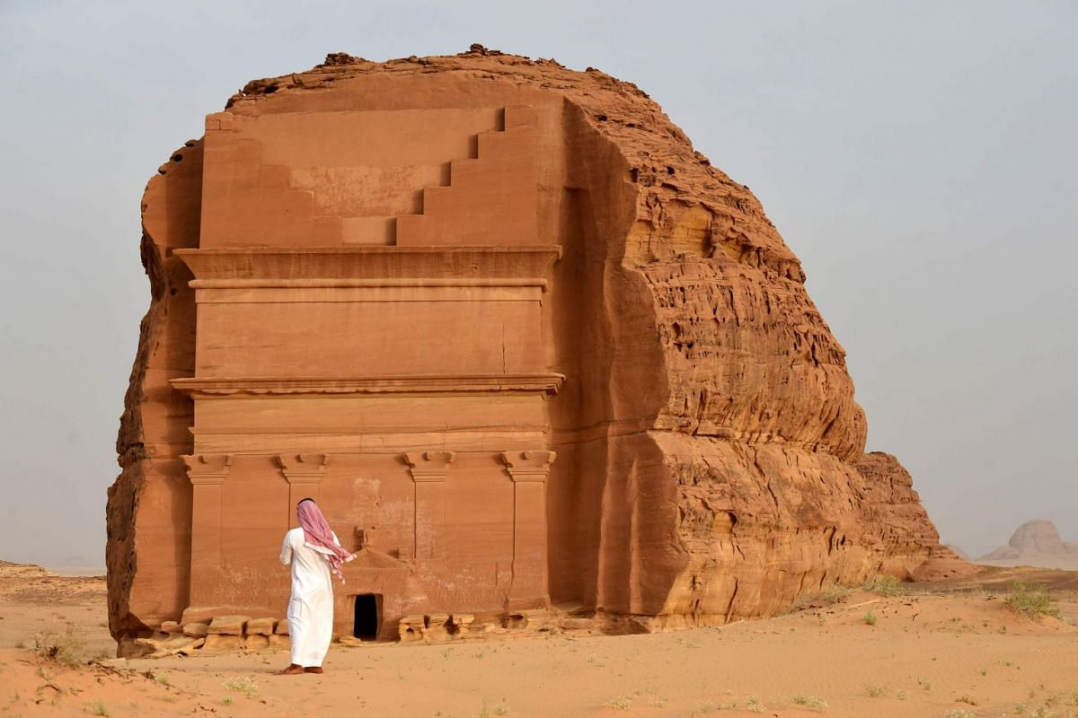 A photo released on April 11, 2018 shows a man standing outside of the Qasr al-Farid tomb (The Lonely Castle) carved into rose-coloured sandstone in Madain Saleh, a UNESCO World Heritage site, near Saudi Arabia's northwestern town of al-Ula on April