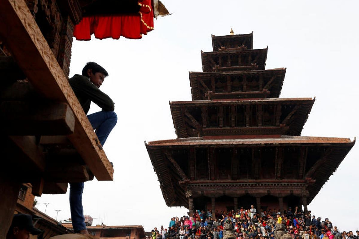 A boy sits on the chariot of God Bhairab as people gather for the Bisket Jatra festival in Bhaktapur, Nepal, on April 10, 2018.