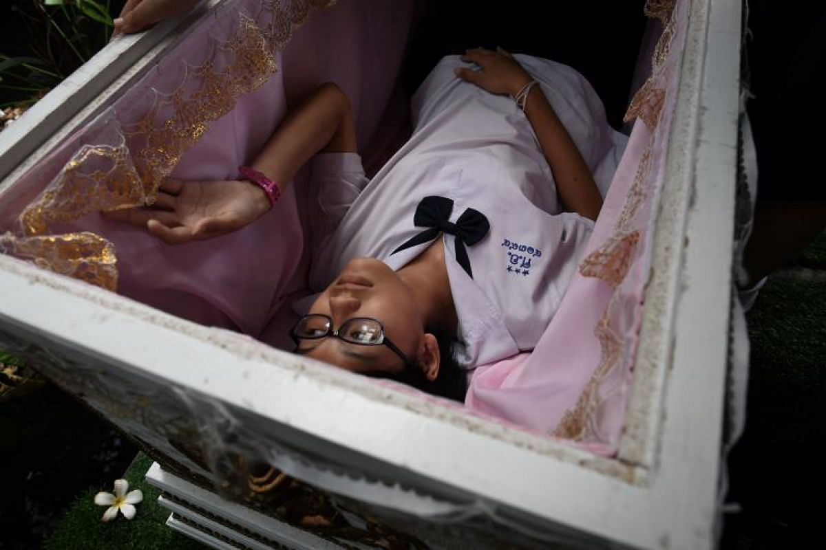 A Thai teenager tries out a traditional coffin at the Kid Mai Death Awareness Cafe.