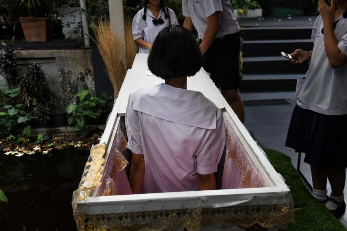 A Thai teenager climbs out of a traditional coffin at the Kid Mai Death Awareness Cafe in Bangkok.