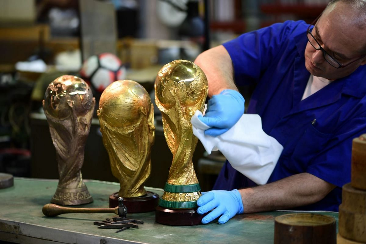 An artisan operator cleans with a cloth a replica of the FIFA football World Cup Trophy at the Italian trophy and medal manufacturer GDE Bertoni on April 11, 2018 in Paderno Dugnano, northern Milan. PHOTO: AFP
