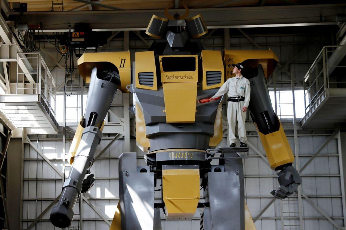 Sakakibara Kikai's engineer Go Sakakibara poses with the bipedal robot Mononofu during its demonstration at its factory in Shinto Village, Gunma Prefecture, Japan, April 12, 2018. PHOTO: REUTERS