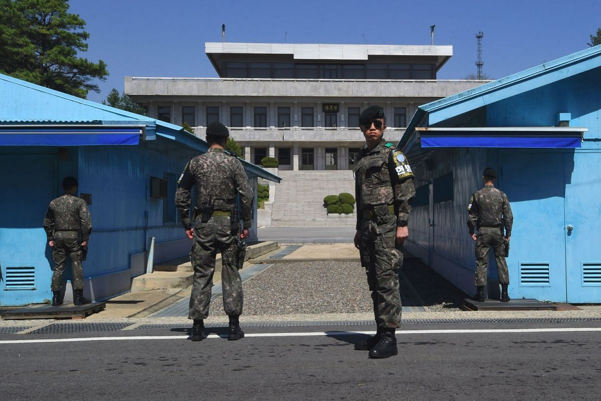 South Korean soldiers stand guard before the military demarcation line during a press tour to the border truce village of Panmunjom in the Demilitarized Zone (DMZ) dividing the two Koreas on April 11, 2018. PHOTO: AFP