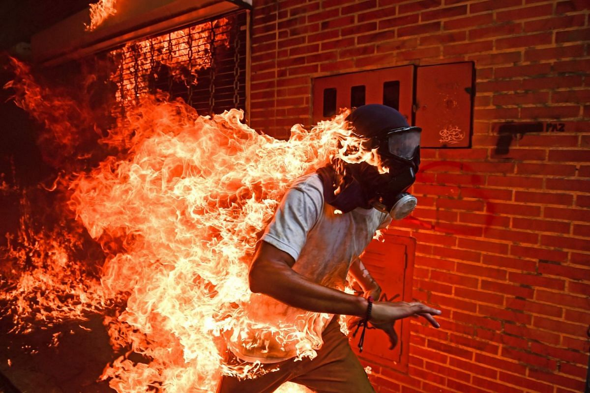 A demonstrator catches fire during clashes with riot police in protest against Venezuelan President Nicolas Maduro in Caracas. This photo, taken on May 3, 2017, by AFP Venezuelan photographer Ronaldo Schemidt, won the World Press Photo Picture Of The