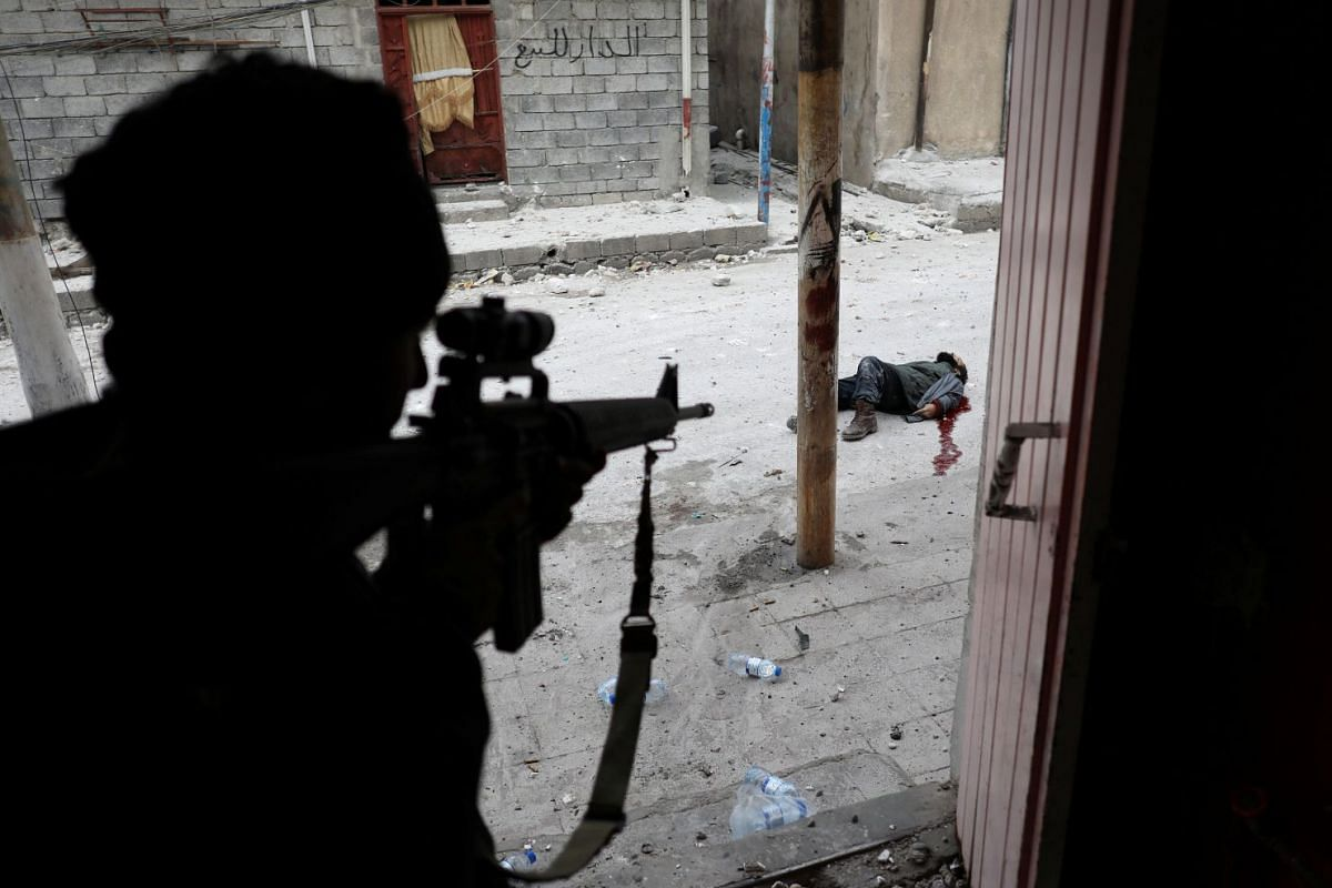 The third-prize winner of World Press Photo 2018 for Spot News Singles, taken by Goran Tomasevic on March 3, 2017, shows an Iraqi Special Forces soldier some moments after shooting dead a suspected suicide bomber during the offensive to retake Mosul