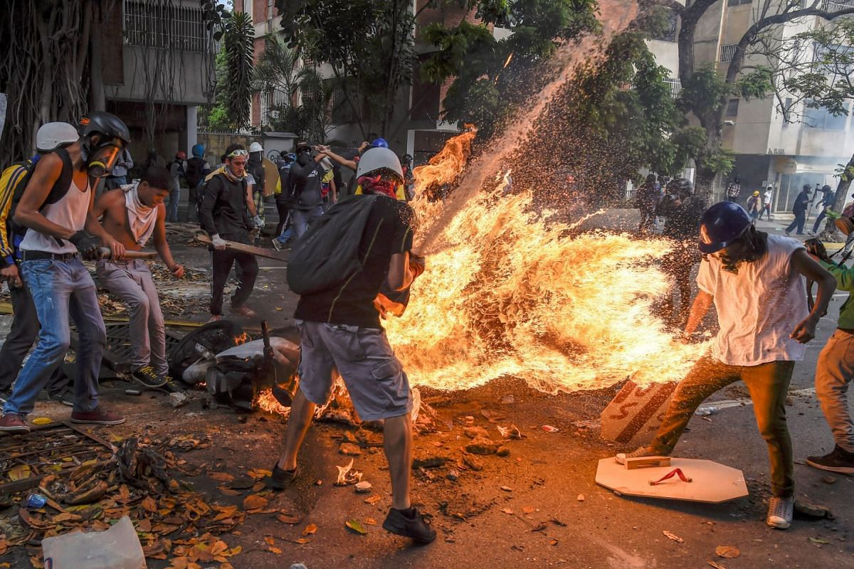 The third-prize winner of World Press Photo 2018 contest for Spot News Stories, comprising photos taken by Juan Barreto on May 3, 2017, shows Victor Salazar catching fire after a motorcycle explodes during a street protest in Caracas, Venezuela.
