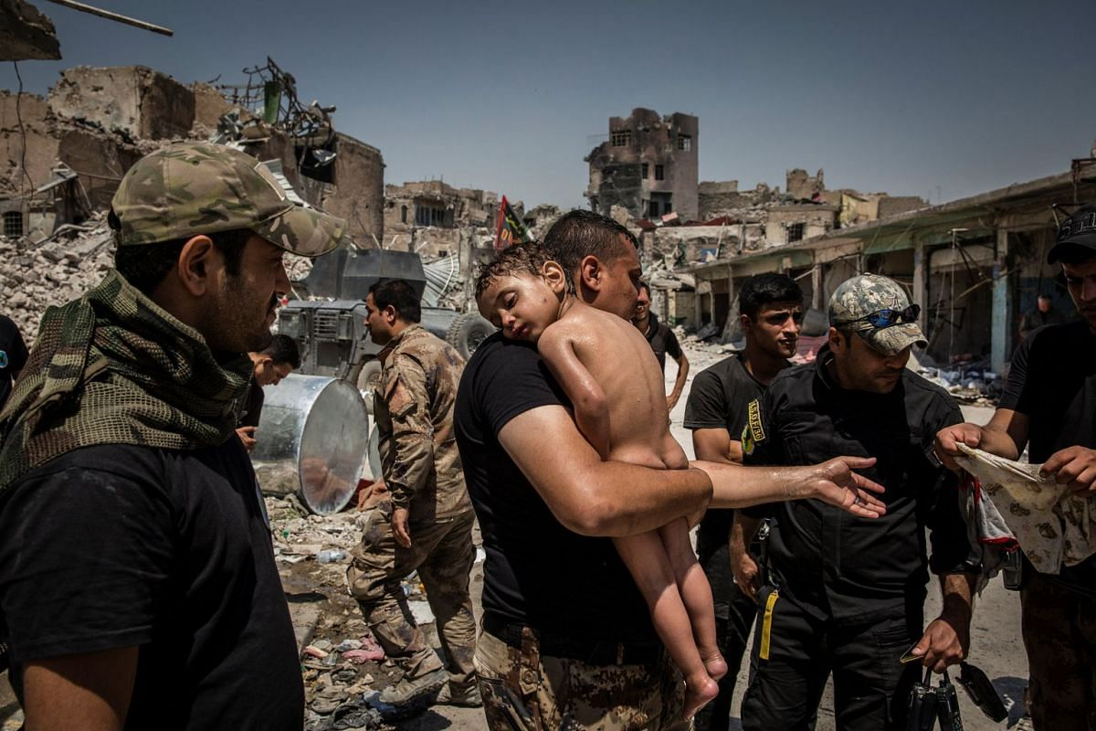 Nominated for the Picture of the Year in World Press Photo 2018, the photo shows an unidentified young boy carried out of the last ISIS-controlled area in the Old City by a man suspected of being a militant and cared for by Iraqi Special Forces soldi