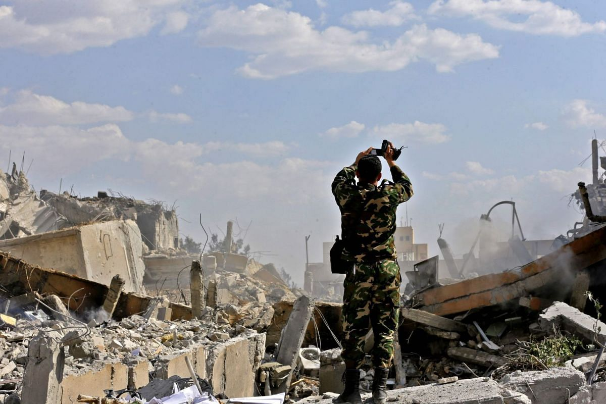 A Syrian soldier inspects the wreckage of a building described as part of the Scientific Studies and Research Centre (SSRC) compound in the Barzeh district, north of Damascus, during a press tour organised by the Syrian information ministry, on April