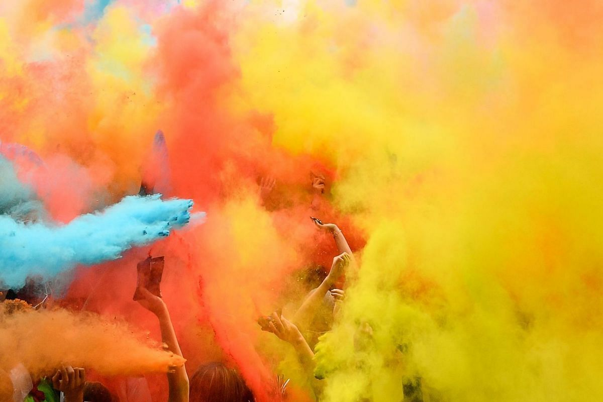 Runners celebrate under coloured powder finishing their five kilometers in the Color Run 2018 at the Eiffel Tower in Paris on April 15, 2018. PHOTO: AFP