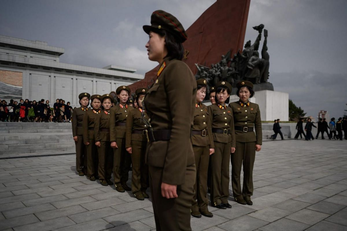 Female Korean People's Army soldiers gather after paying their respects before the statues of late North Korean leaders Kim Il Sung and Kim Jong Il at Mansu Hill.