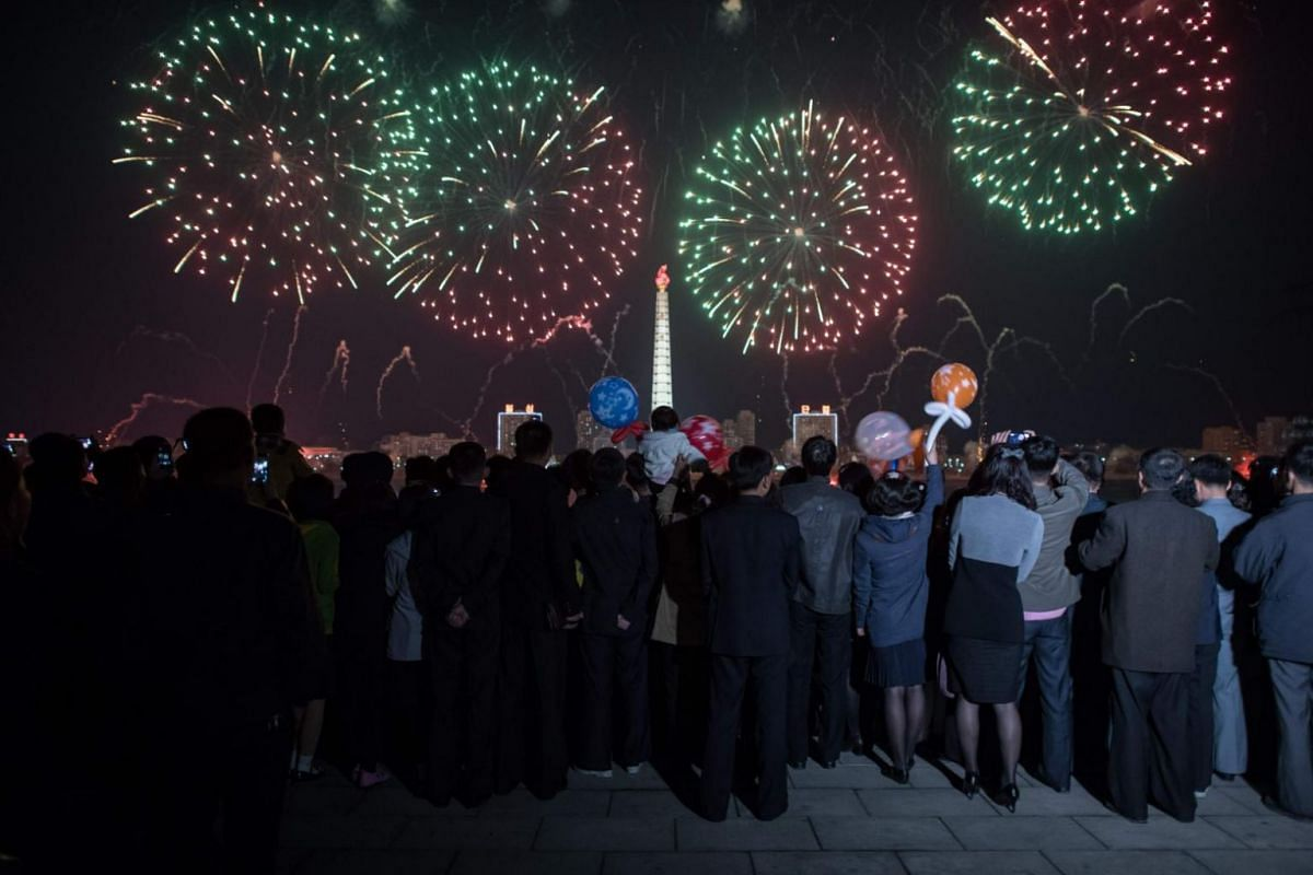 Spectators stand before a fireworks display over the Taedong river during celebrations marking the anniversary of the birth of late North Korean leader Kim Il Sung.