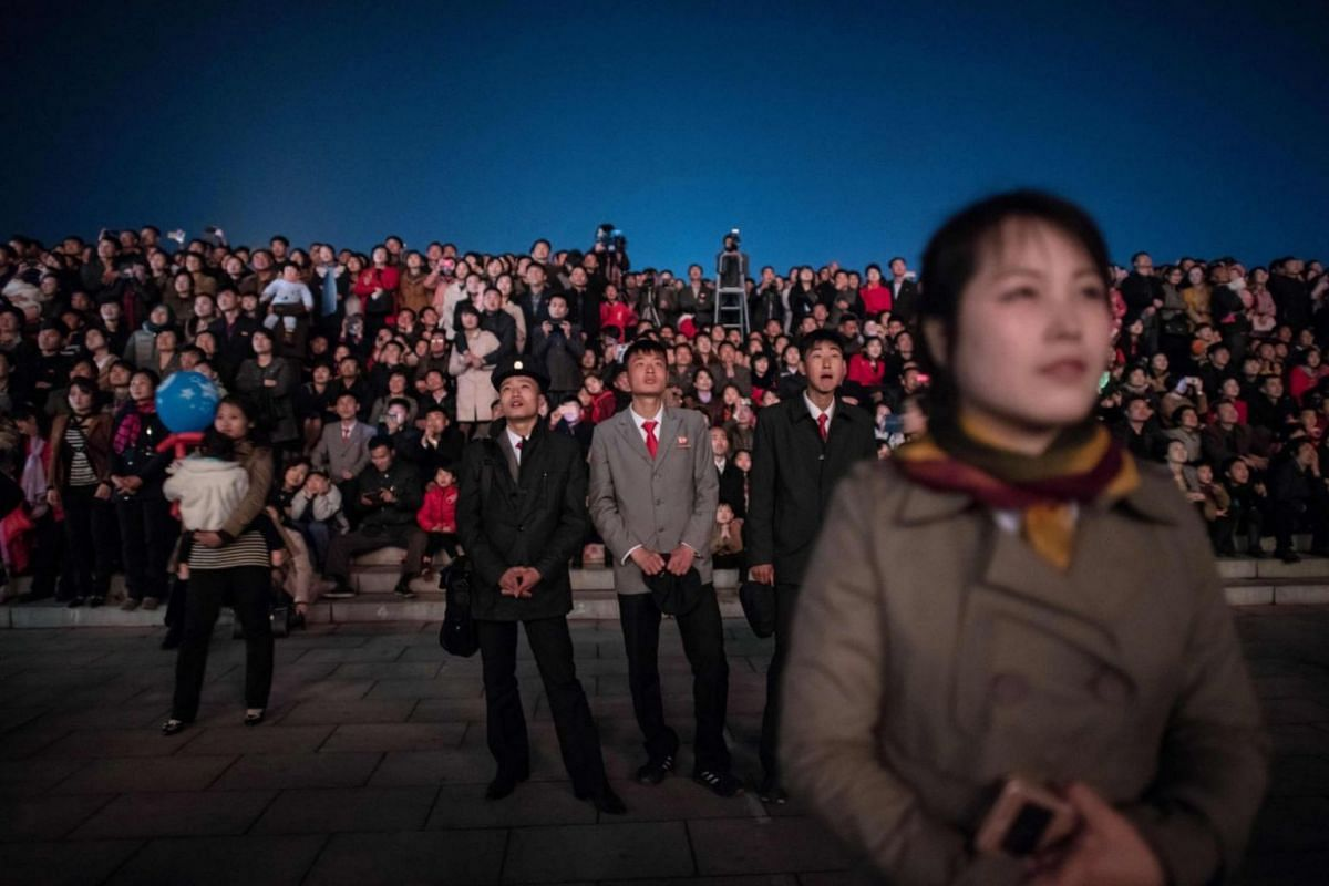 Spectators react during the fireworks display over the Taedong river.