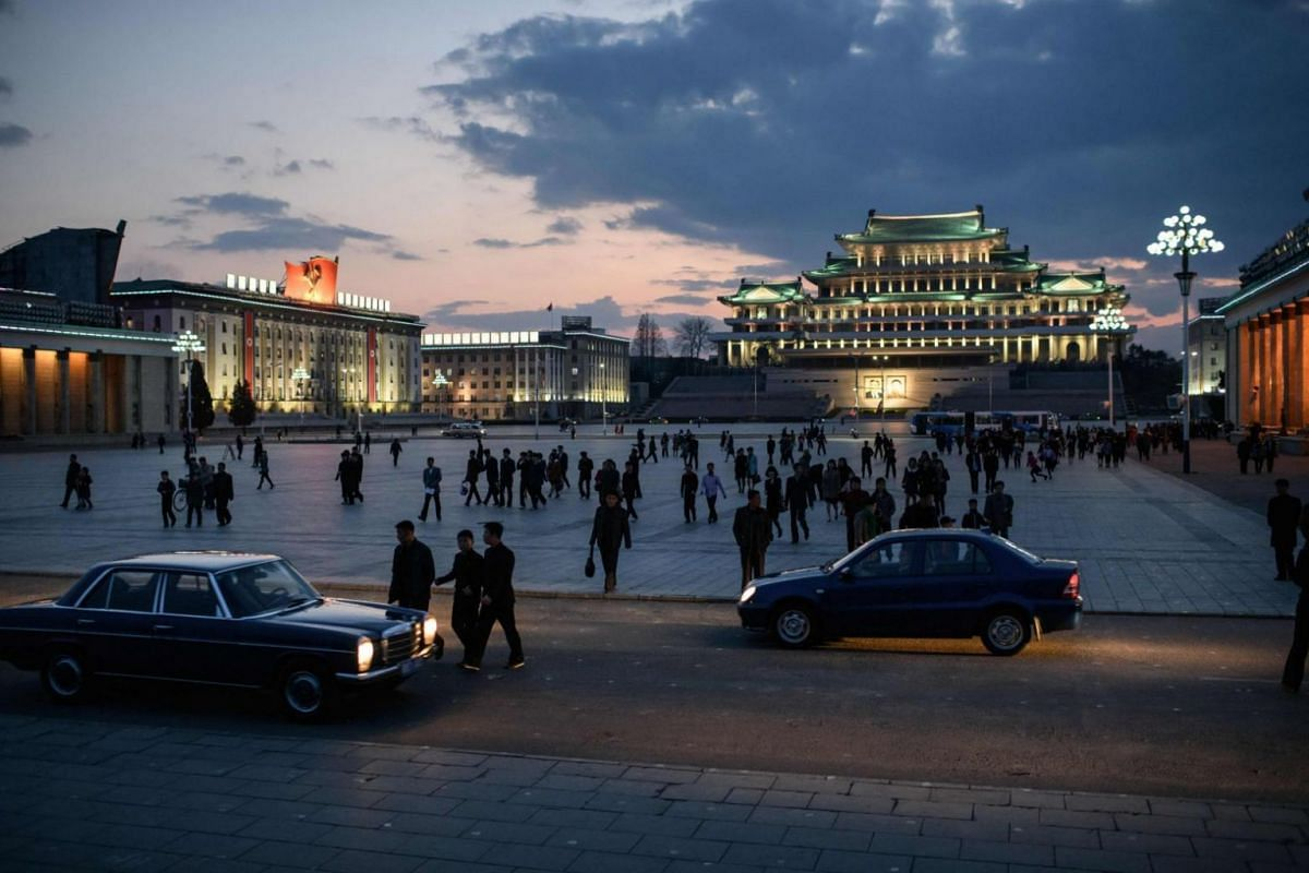 Spectators walk across Kim Il Sung square as they arrive to watch a fireworks display.