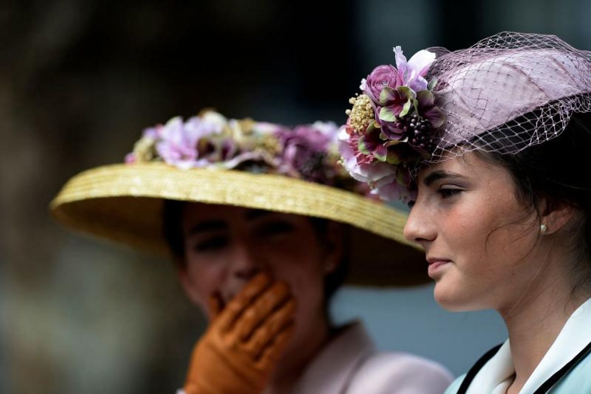 Participants wearing period dresses wait for parading in the XXXIII Enganches (Horse-drawn carriages) exhibition at the Real Maestranza bullring in Sevilla on April 15, 2018.