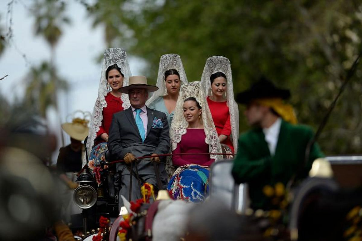 Participants sporting traditional mantillas (shawls) wait for parading in the XXXIII Enganches (Horse-drawn carriages) exhibition at the Real Maestranza bullring in Sevilla on April 15, 2018.