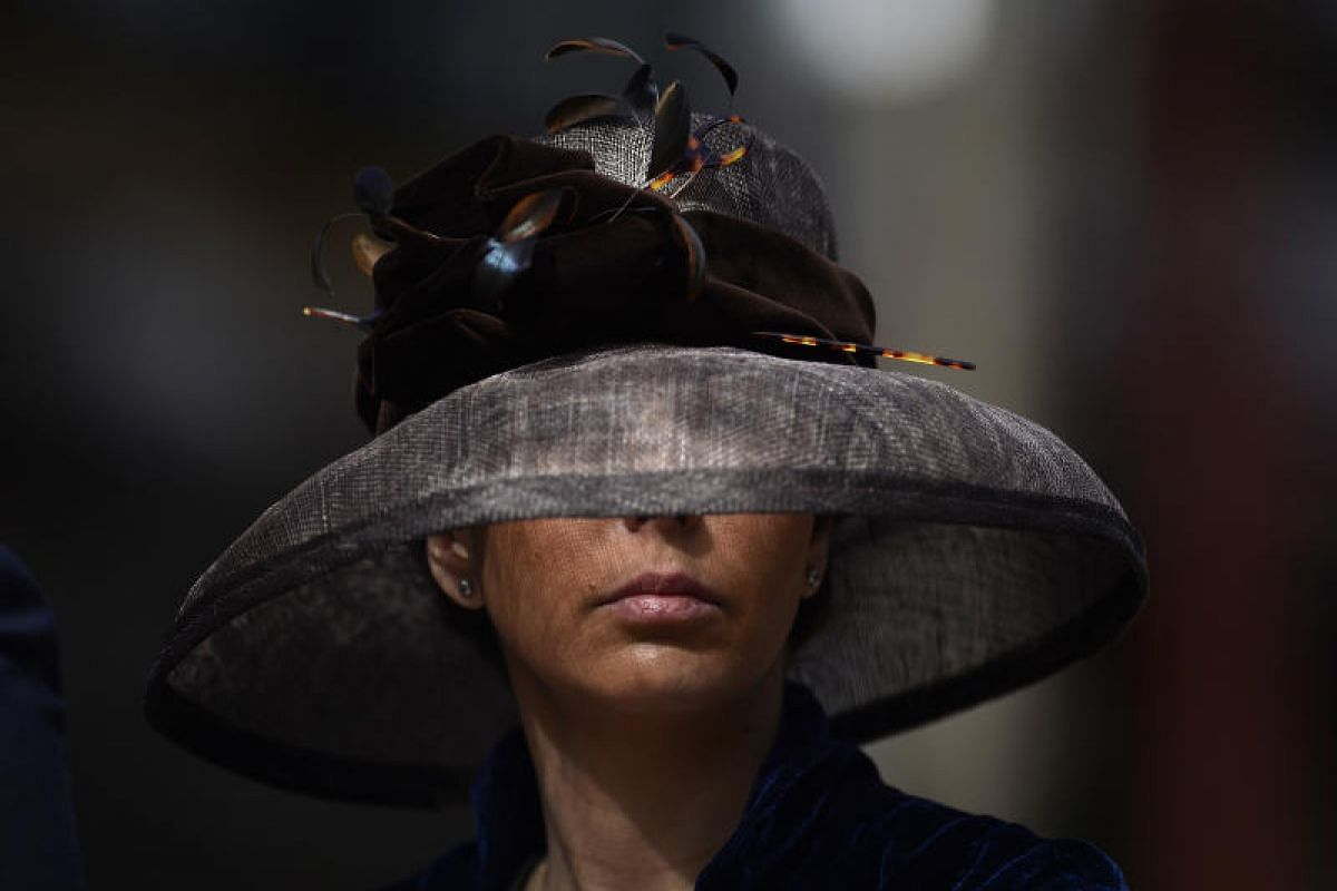 A woman sporting a pamela hat participates in the XXXIII Enganches (Horse-drawn carriages) exhibition at the Real Maestranza bullring in Sevilla on April 15, 2018.