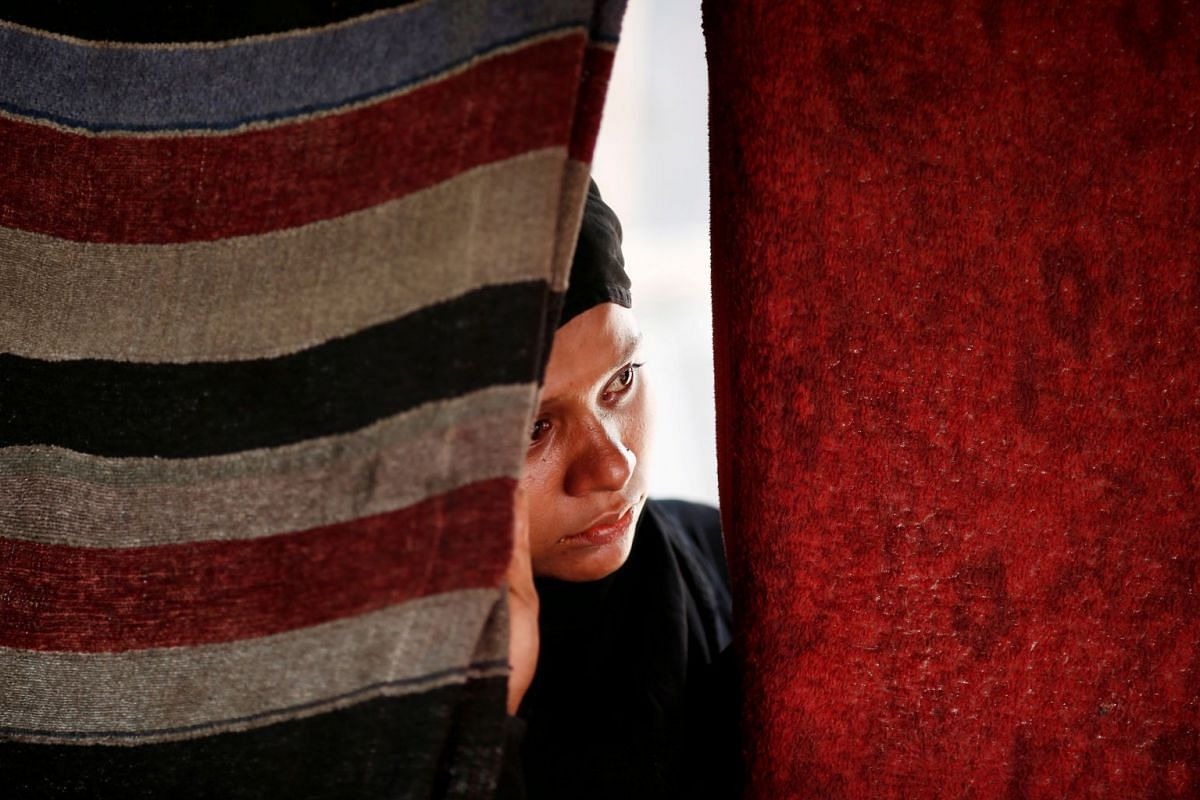 A woman stands behind a curtain inside a temporary shelter after a fire broke out in a Rohingya camp in New Delhi, India, April 15, 2018. PHOTO: REUTERS