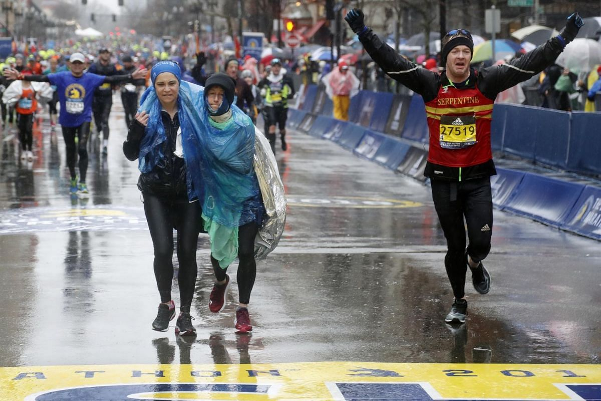As one runner helps another runner, Matthew Williams of London raises his arms as he crosses the finish line in the 2018 Boston Marathon on Apr 16, 2018 in Boston, MA, USA. PHOTO: USA TODAY SPORTS