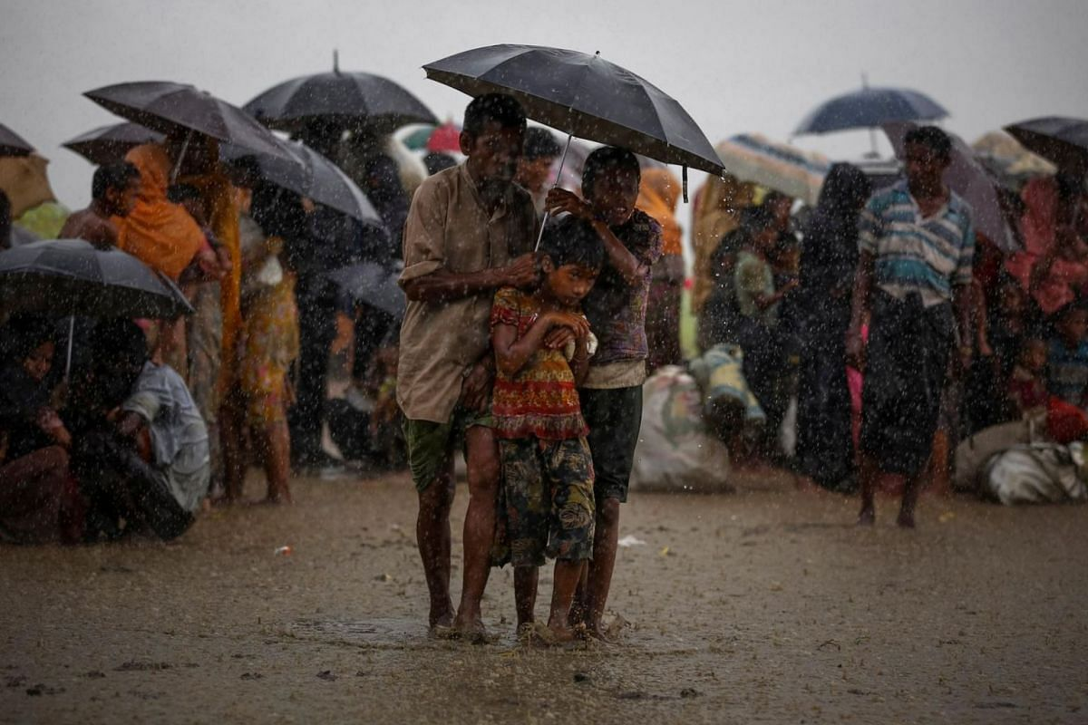 Rohingya refugees try to take shelter from torrential rain as they are held by the Border Guard Bangladesh after illegally crossing the border in Teknaf, Bangladesh, on Aug 31, 2017.