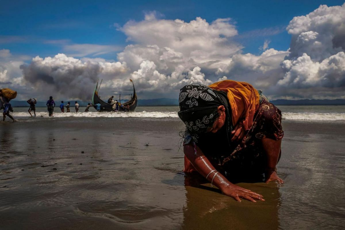 An exhausted Rohingya refugee woman touches the shore after crossing the Bangladesh-Myanmar border by boat through the Bay of Bengal, in Shah Porir Dwip, Bangladesh, on Sept 11, 2017.